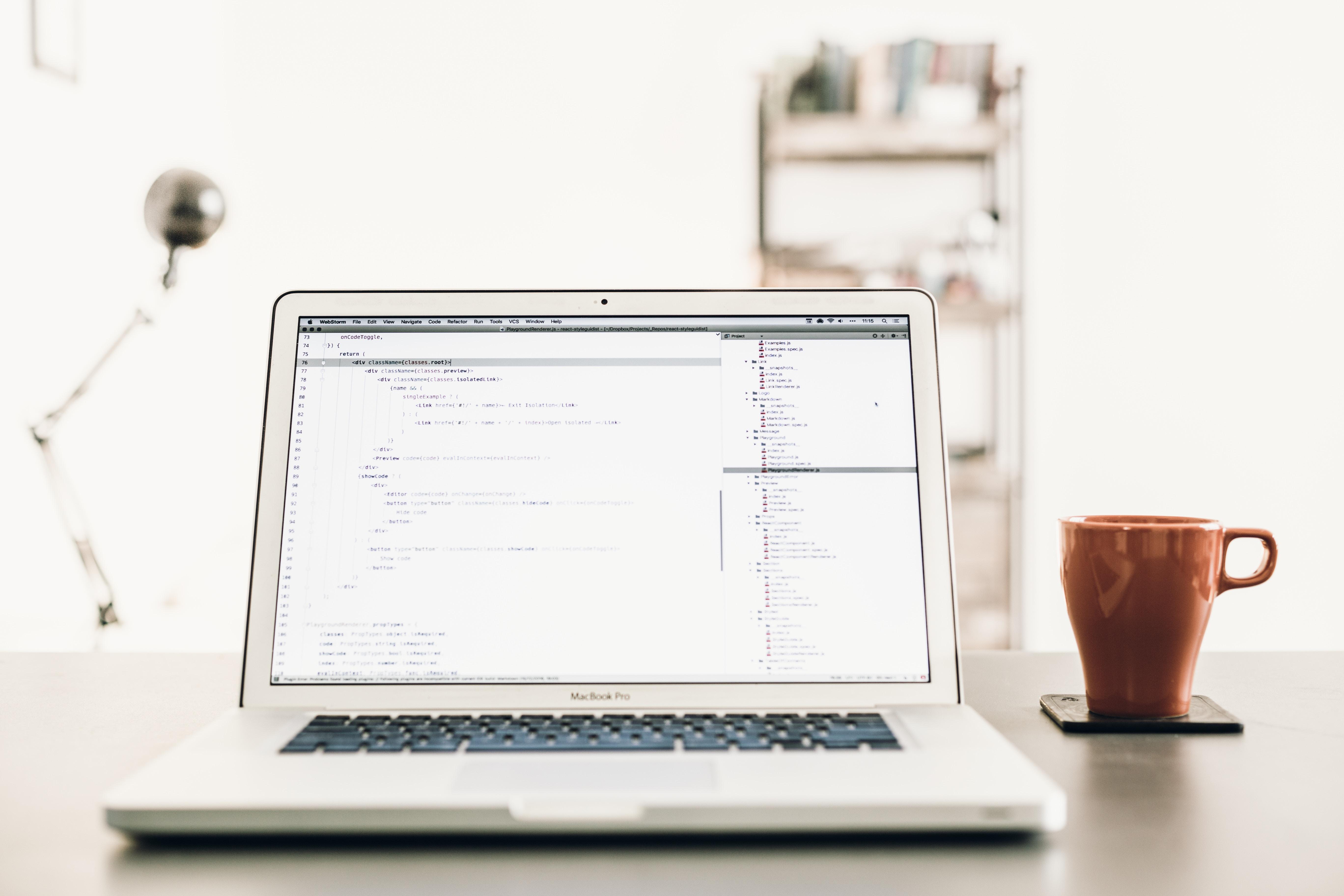 Open macbookPro on desk next to coffee mug