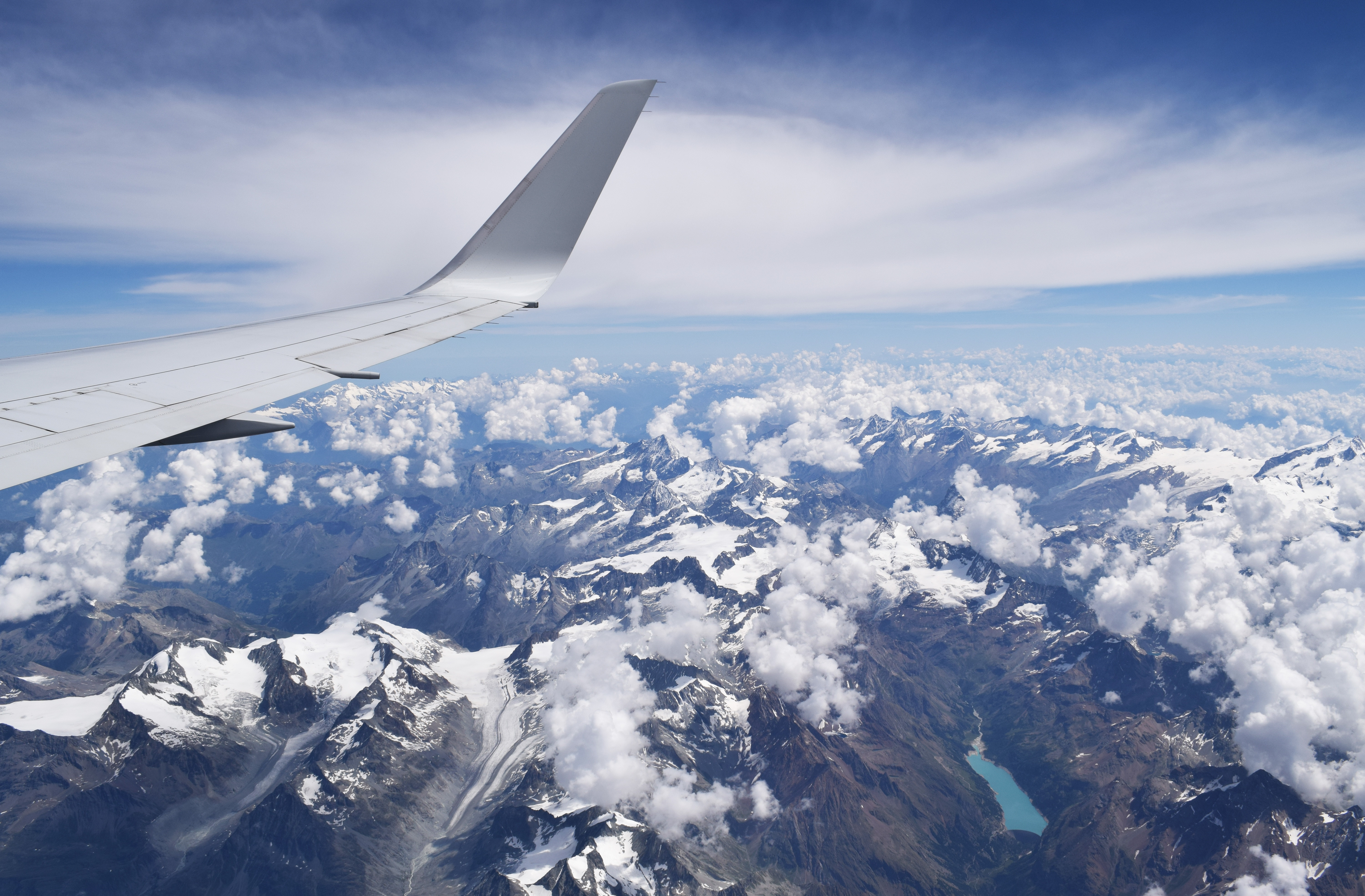 flying over mountain range with some clouds