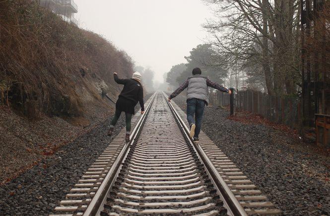 A couple balancing on train tracks