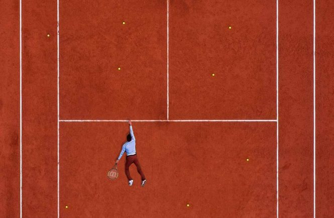 A flipped tennis court, with a man hanging on for dear life