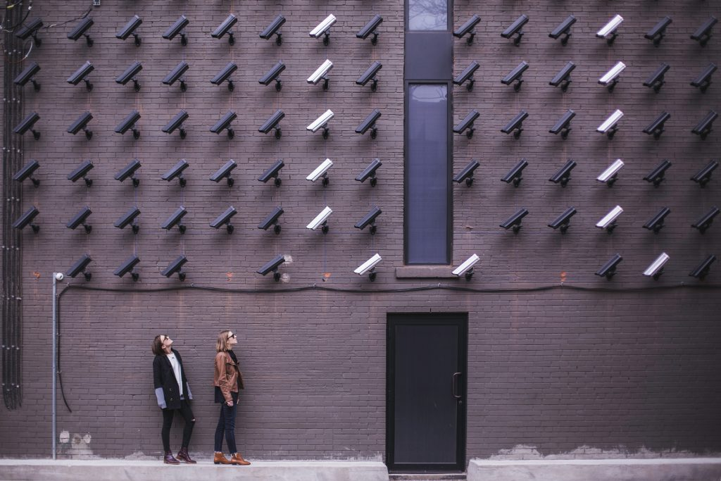 Woman looking up at several security cameras
