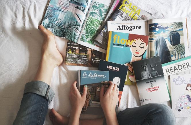 woman surrounded by books on a bed