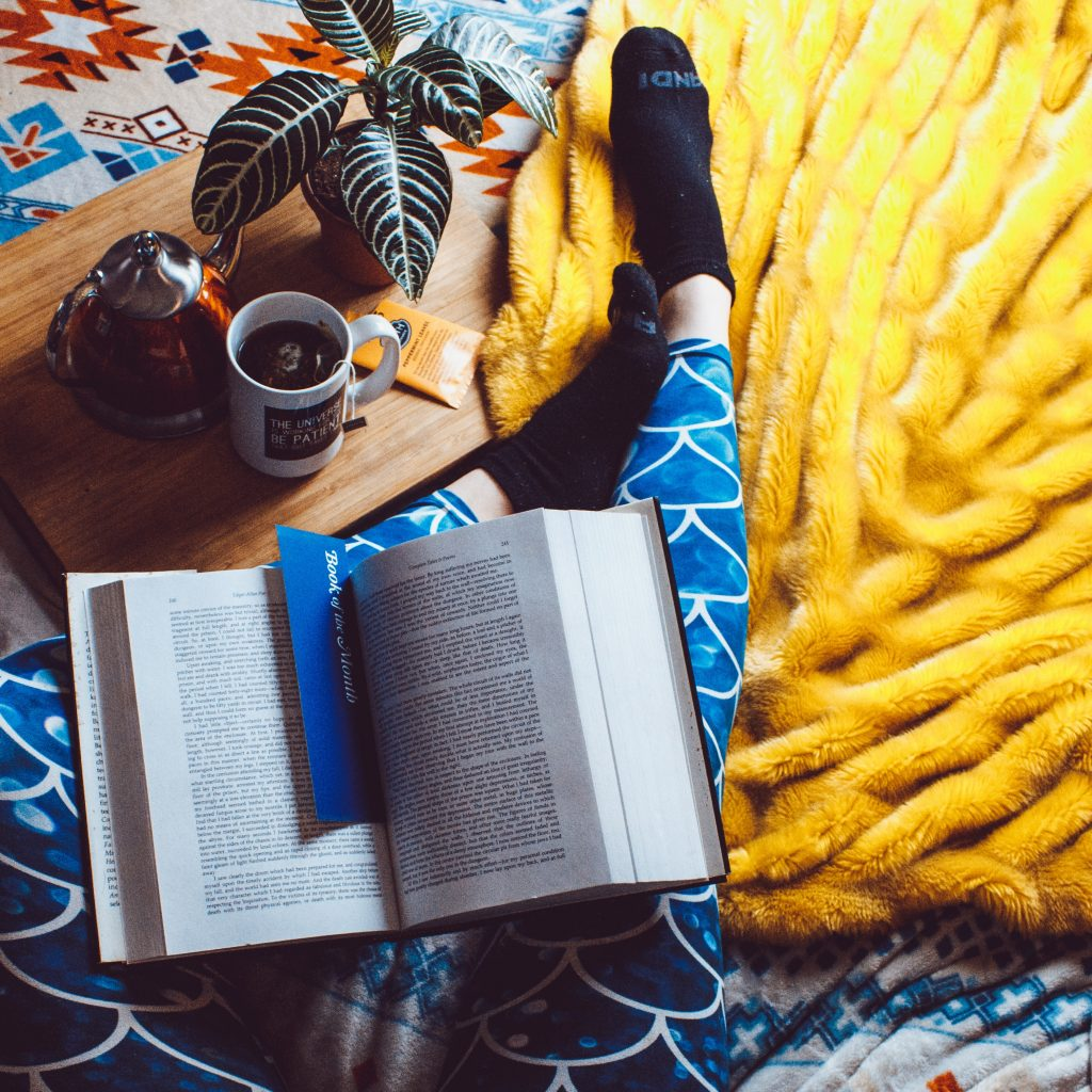 person with open book on legs and coffee